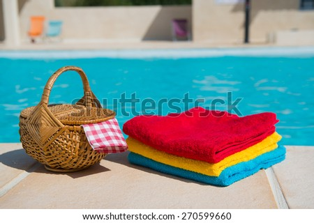 Towels and picnic at te swimming pool - stock photo