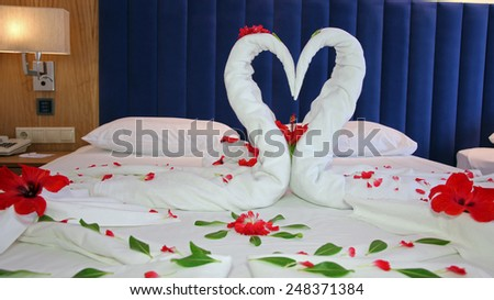 Towels arranged as swans on the bed in hotel room. Romantic Flower Petal Arrangement on a Hotel Bed. Honeymoon bed decorated with red petals and towels. Swans Made from Towels Surround by Red Petals. - stock photo
