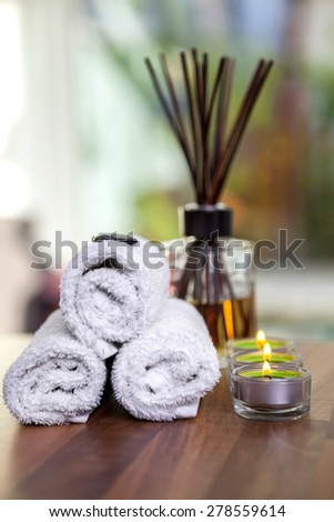 towels, candles, hot stones and scent sticks on wooden background shot front on hot stones on top of towels candles n a side - stock photo