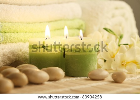towels candles stones and freesias - stock photo