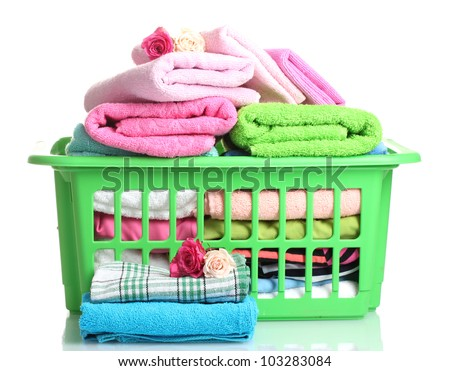 Towels in green plastic basket isolated on white - stock photo