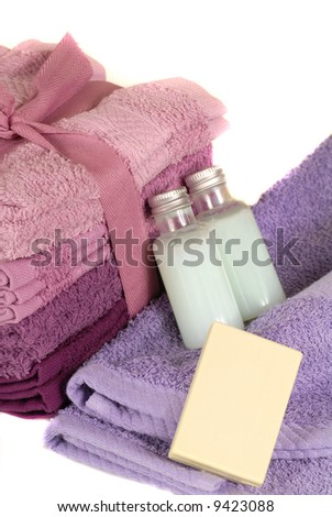Towels in shapes of purple with soap and shampoo - stock photo
