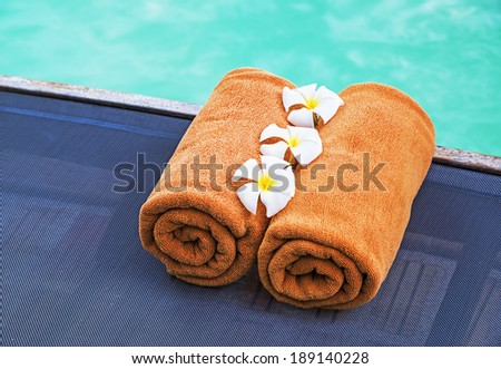 Towels on pool chairs near swimming pool  - stock photo