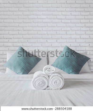 towels on the white bed - stock photo