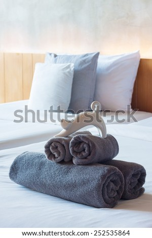 Towels roll on bed in modern hotel room. - stock photo