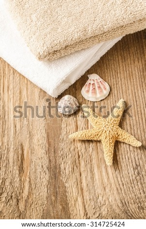 Towels, shells and a starfish on wooden table
