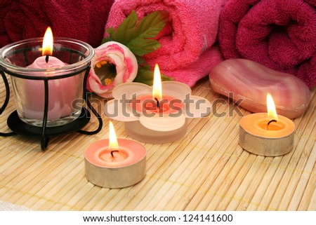 Towels, soap, candles and flower on mat background. - stock photo