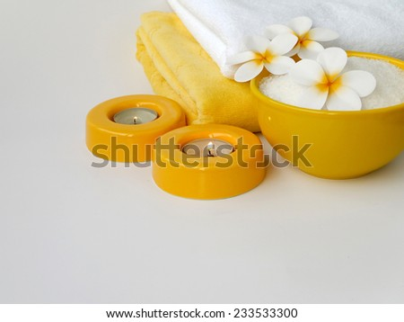 Towels, two candles, three frangipani flowers and salt  - stock photo