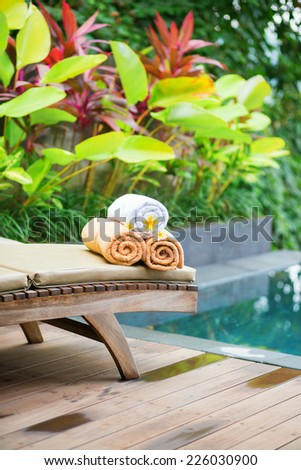 Towels with white frangipani flowers in a Balinese spa - stock photo