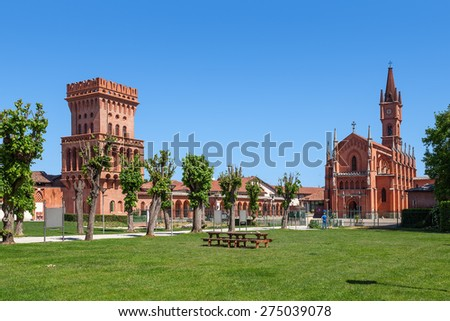 Tower and catholic church under blue sky in small town of Pollenzo in Piedmont, Northern Italy. - stock photo