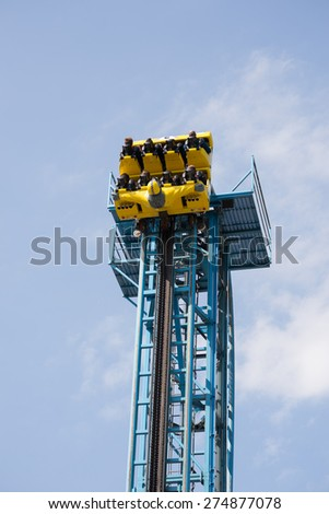 Tower and wagon with people of a rollercoaster before a free fall - stock photo