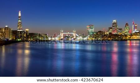 Tower Bridge and cityscape of London at night, UK - stock photo