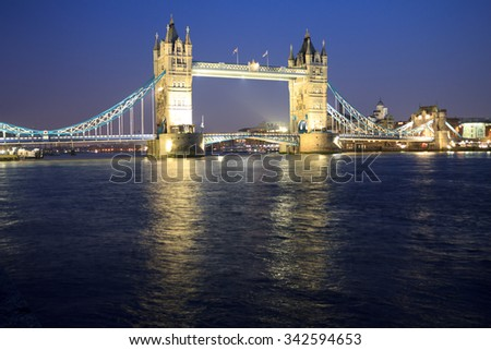 Tower Bridge at night in the calm River Thames, London, England