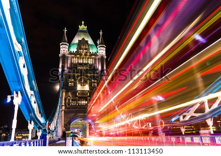 Tower Bridge in London, UK at night with moving red double-decker bus leaving light traces - stock photo