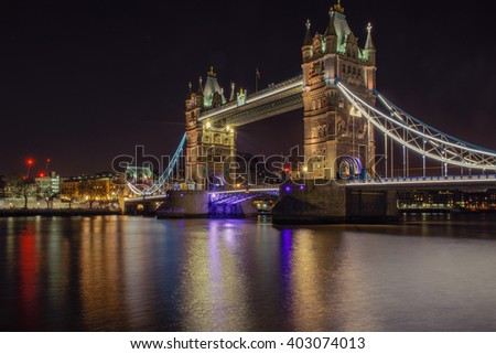 Tower Bridge in London, UK, illuminated at night time with reflection from Thames