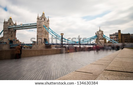Tower Bridge, London with pedestrians on sidewalk - stock photo
