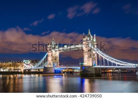 Tower Bridge reflecting on the River Thames at night, London, UK - stock photo