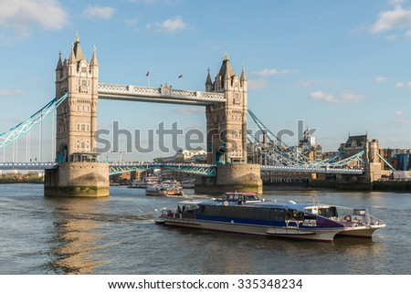 Tower Bridge (Symbol of London City Skyline Landmark) and Thames Clippers cruise under Clear Blue Sky at Sunset in Summer. River Bus Boat Commuter and Tourist service on the River Thames, England, UK - stock photo