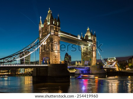 Tower Bridge with reflections in the thames river at night in London - stock photo