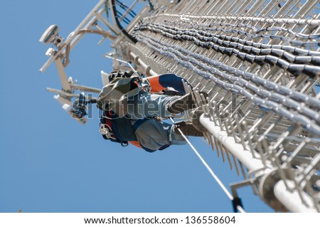 Tower climber and working on cellular tower system. - stock photo
