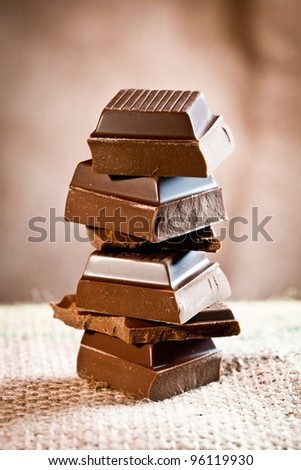 Tower composed of pieces of staple chocolate on a linen background for chocolate and cocoa concepts.
