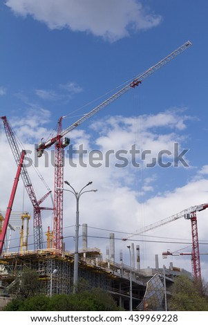 Tower crane and construction stadium. Big construction crane and the building against the sky background. Tower Crane in Construction site. - stock photo