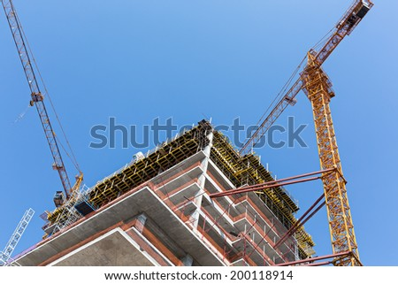Tower crane and unfinished building against blue sky - stock photo
