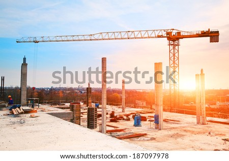 tower crane at construction site in morning sunlight - stock photo