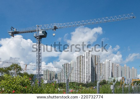 Tower Crane in the construction site, with tall buildings at the back - stock photo