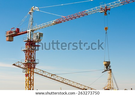 Tower crane lifting up a cement bucket at construction area against blue sky - stock photo