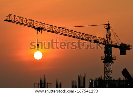 Tower crane on a construction site at sunrise - stock photo
