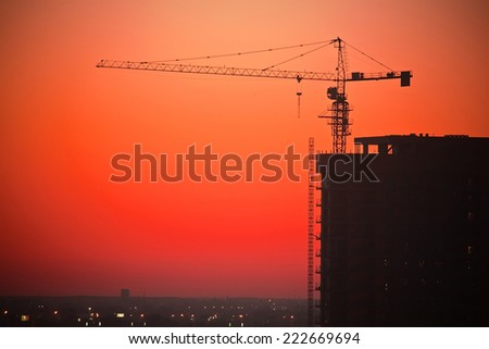 Tower crane on a construction site at sunset - stock photo