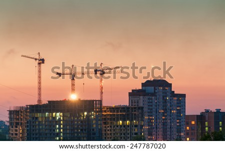 Tower cranes on construction site of modern buildings and skyscrapers against evening glow background. Moscow, Russia. - stock photo