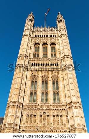 Tower in the building of British Parliament with red bus