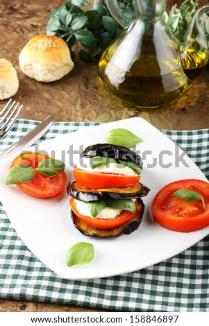 Tower of aubergine, mozzarella and tomato on complex background