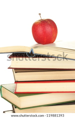 Tower of books with apple on white background close-up