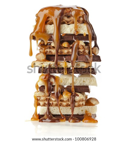 Tower of Chocolate caramel syrup poured on chocolate pieces,nuts, cookies - stock photo