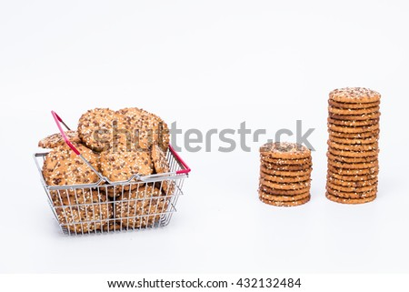 Tower of tasty cookies  and shopping basket full of cookies with sesame and flax seeds isolated with white background  - stock photo