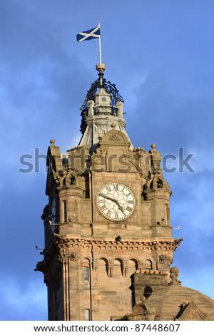 Tower of the Balmoral Hotel before blue sky, Edinburgh - stock photo