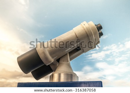 Tower viewer against blue cloudy sky. Vivid photography of sightseeing binocular as a metaphor for touristic destinations, forecasting or planning and business analysis.