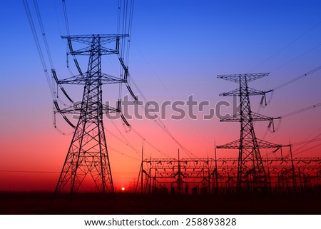 Towering high voltage towers and power site under the setting sun