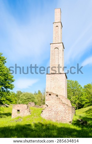 Towering smokestack left standing among ruins after an old factory. Green nature surrounding it. Blue sky with clouds. - stock photo