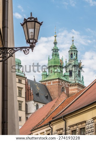 Towers of the cathedral of St Stanislaw and St Vaclav and royal castle on the Wawel Hill, Krakow, Poland, seen from the Kanonicza street - stock photo