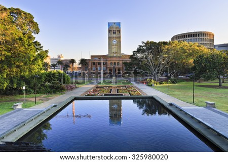 town-hall of the city of Newcastle behind still pool in a park decorated by blooming flowers at sunrise - stock photo