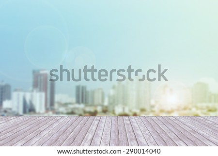 town of blurred blue color and wooden terrace space front with lighting flare