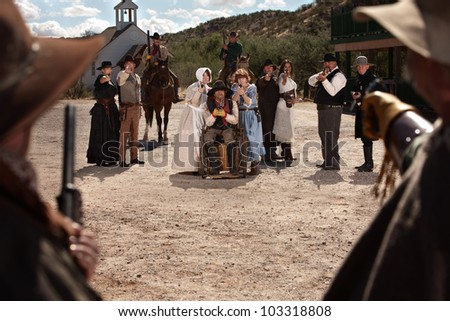 Townspeople under attack from bandits in old west scene - stock photo