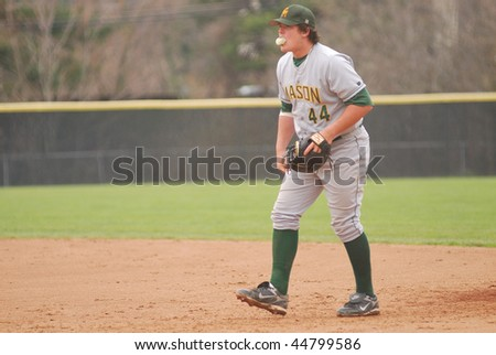 TOWSON, MD - APRIL 6: George Mason University baseball player Justin Bour blows a bubble while playing defense in the April 6, 2008 game in Towson, MD