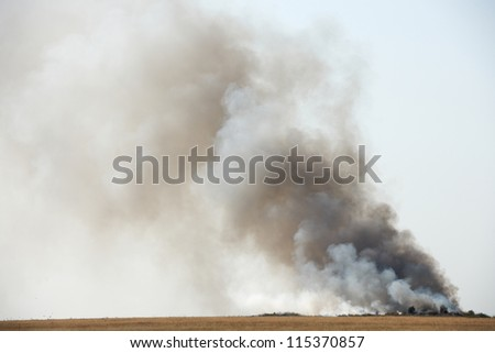 Toxic black smoke from fire in dung-hill emitting poison in the air