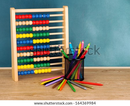 Toy abacus and pencils on table, on school desk background - stock photo