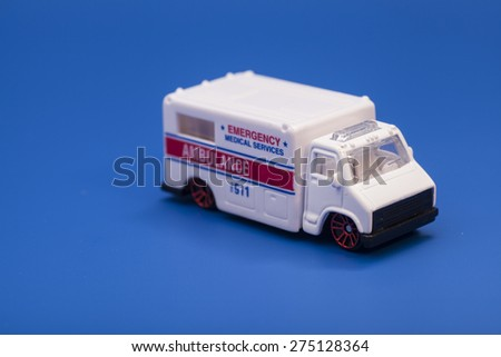 Toy ambulance car isolated on blue background - stock photo